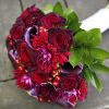 Deep red carnation and rose hand-tied bouquet, with purple accents